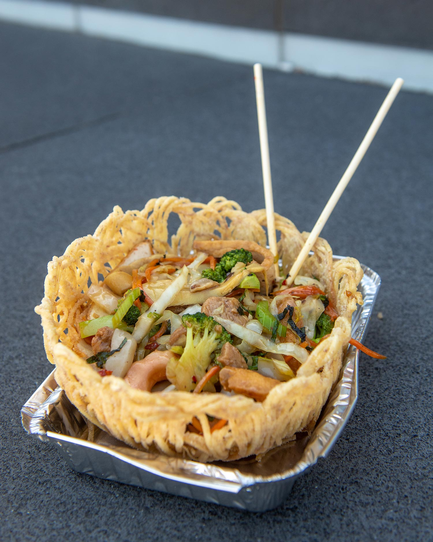 Photo of Grasshoppers' Crispy Taro Nest on N Beacon St, Allston, Marsh 23. Crispy taro strands form a bowl that holds a noodle salad with broccoli, onions and other vegetables.