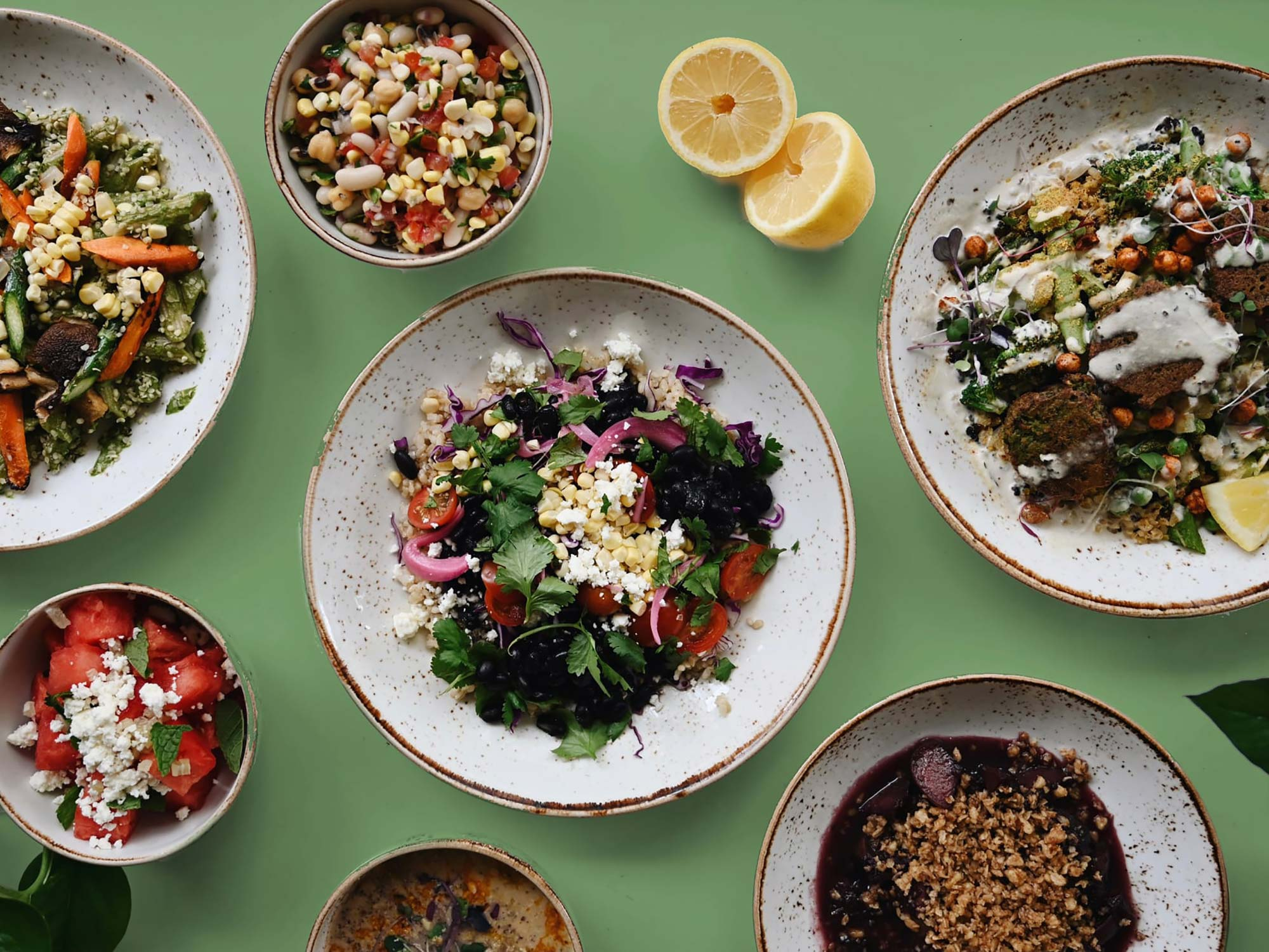 Photo of Life Alive Spring Meal Plan.  The photo shows several rustic-looking bowls filled with greens, vegetables, falafel and other ingredients, topped with a cheese or sauce.  The plates rest on a green surface.