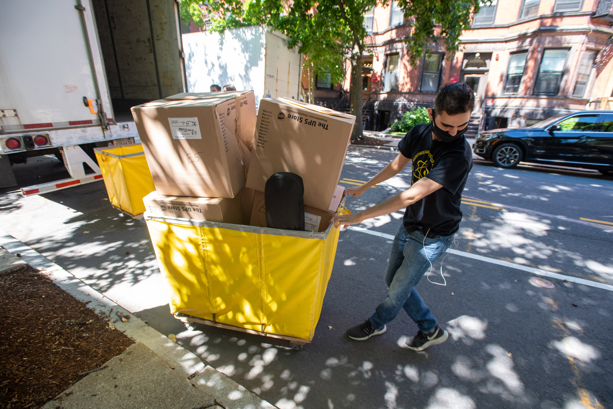 Photo of August Menchaca (CAS'23) in a face mask, black t-shirt and jeans, collects his things from a UPS truck and wheels them away in a yellow cart while moving in on Bay State Rd on August 26.