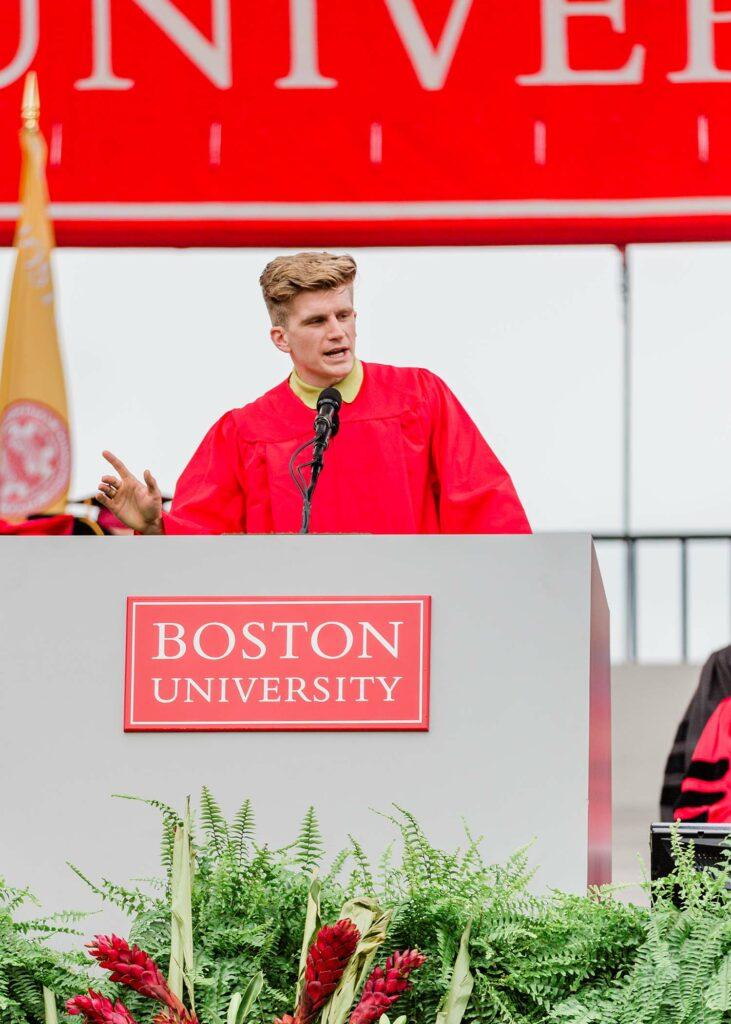 Photo of student speaker Macken Murphy (CAS'20), in his red robe, speaking on the podium.