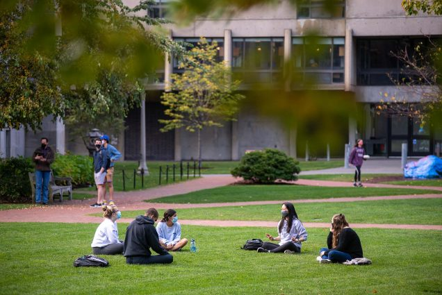 Photo of groups on BU Beach on Oct 23, 2020 safely conversing. A group of five seated in the grass sits socially distanced. In the background other students are seen conversing in small groups with masks on.