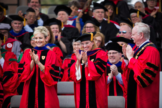 Photo of Ryan Roth Gallo (LAW'99), pictured (left) at the 2018 BU Commencement in full regalia. On the right, Carmen Yulín Cruz Soto (CAS'84) and President Brown are seen. All of them clap, and rows of commencement go-ers in regalia are seen behind them.