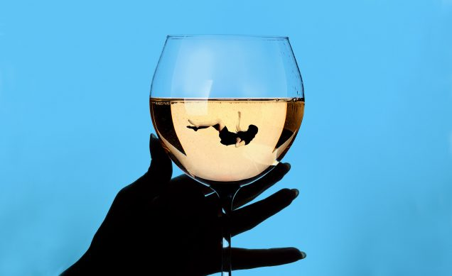 Illustration of a hand darkened in silhouette holding a wine glass filled with a wine white. In the wine glass, a woman floats as if she's fallen in. The background is bright blue that darkens around the edges.