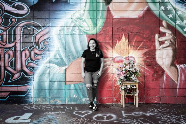Photo of Daisy Figueroa (LAW'21) in a black t-shirt and jeans ripped at the knee standing if front of a larger mural with the virgin mary and graffiti painted all over it. The photo has been edited so Figueroa is in black and white and the mural is brightly colored.