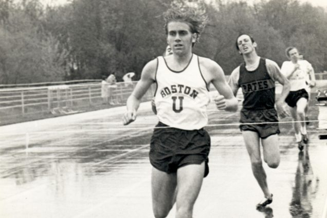 Black and white photo of Tom Beatty (CAS'72) during a historic track meet. He wears a BU jersey and his hair bounces as he runs ahead of two competitors on a track.