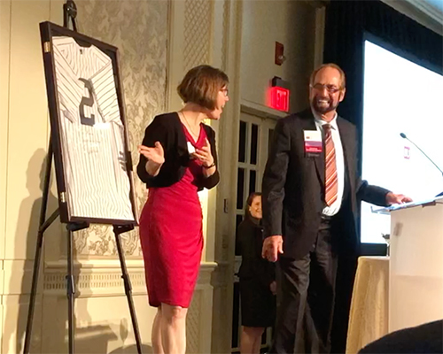 Gerry Cohen ('62) presents Dean O'Rourke with a jersey signed by Yankees player Derek Jeter