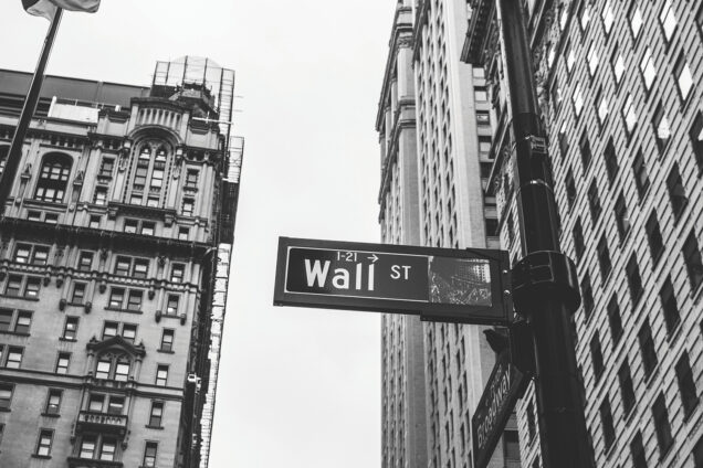 A black and white photo of the street signs at the intersection of Wall St. and Broadway in New York City