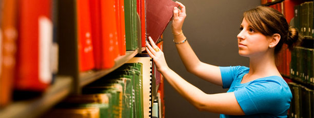 Student taking a book off of a shelf