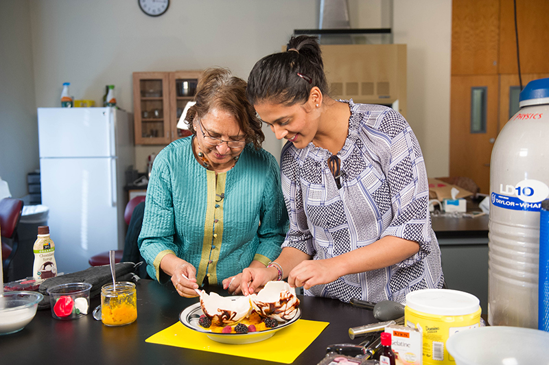 "Rama Bansil, a College of Arts & Sciences professor of physics (left), and Shivangi Surana (SHA'16) try their hand at liquid nitrogen ""cooking."""