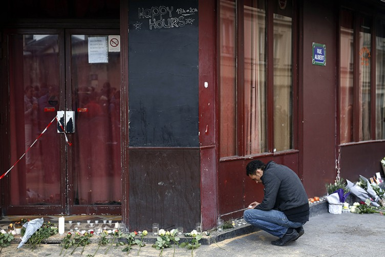 A man places a candle in front of the Carillon cafe in Paris Saturday, November 14, 2015, a day after over 120 people were killed in a series of shooting and explosions. AP Photo/Jerome Delay