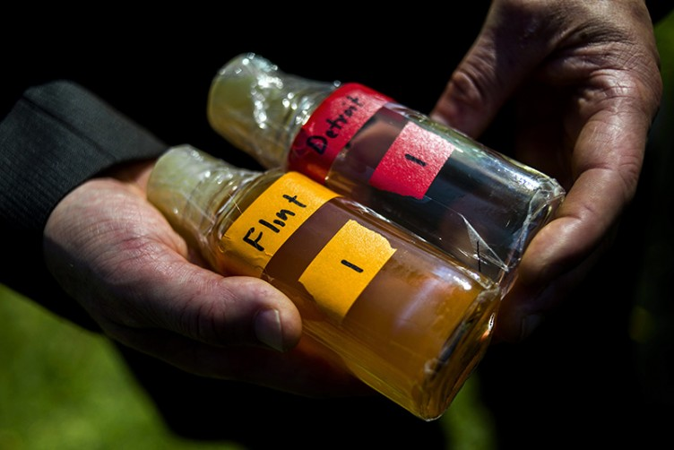 Virginia Tech professor Marc Edwards shows the difference in water quality between Detroit and Flint after testing, giving evidence after more than 270 samples were sent in from Flint that show high levels of lead during a news conference on Tuesday, Sept. 15, 2015 outside of City Hall in downtown Flint, Mich. (Jake May/The Flint Journal via AP) MANDATORY CREDIT LOCAL TV OUT; LOCAL INTERNET OUT