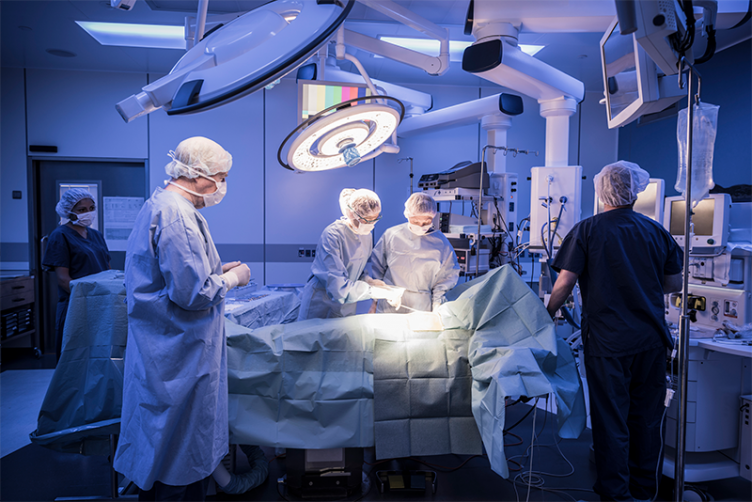 Surgeons and nurses operate in a hospital operating room