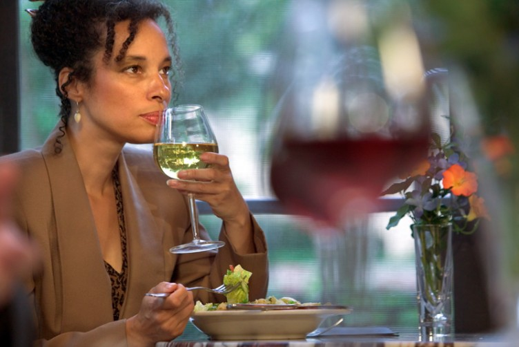 African American woman drinking wine with dinner