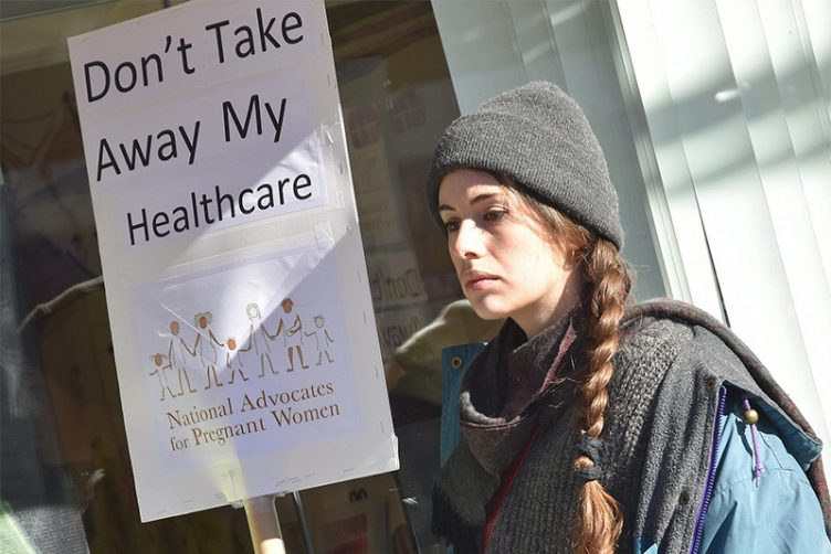 a woman holds a sign that says Don't Take Away My Healthcare outside of NY Representative Dan Donovan's office during a rally urging Republicans to preserve the Affordable Care Act, Staten Island, NY