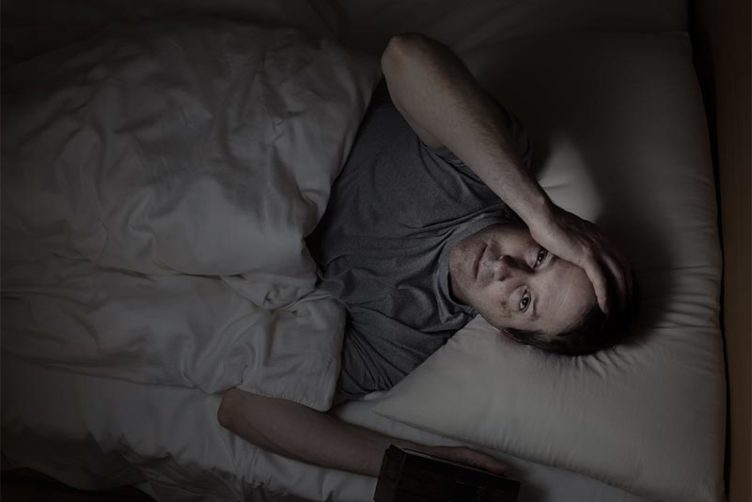 Man in bed with insomnia experiencing a lack of REM sleep
