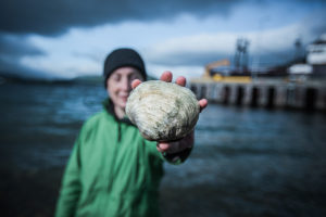 Professor of Archaeology Catherine West holds a clamshell in Dutch Harbor middens where she studies ancient climate change adaptation in the Aleutian Islands.