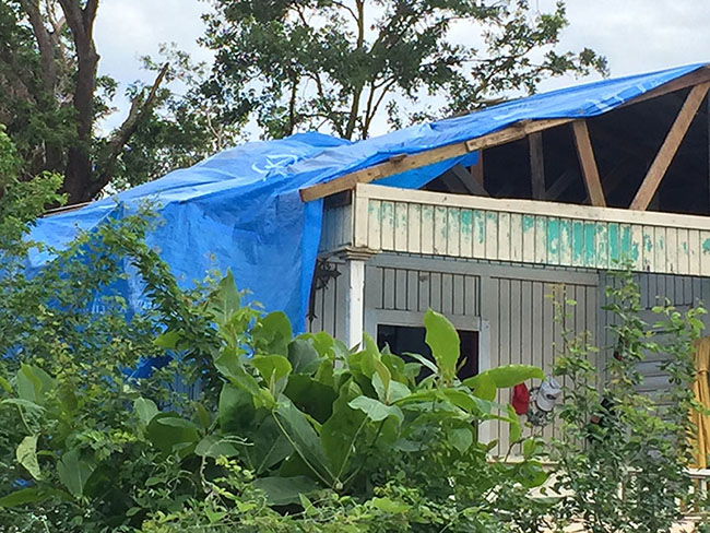 A blue tarp covers the destroyed roof of a house in Puerto Rico in the aftermath of Hurricane Maria