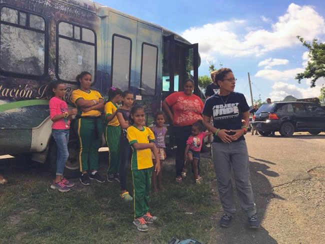 Boston Medical Center psychiatrist Lisa Fortuna stands with school children and school bus in Puerto Rico during a Project Hope relief trip in the aftermath of Hurricane Maria