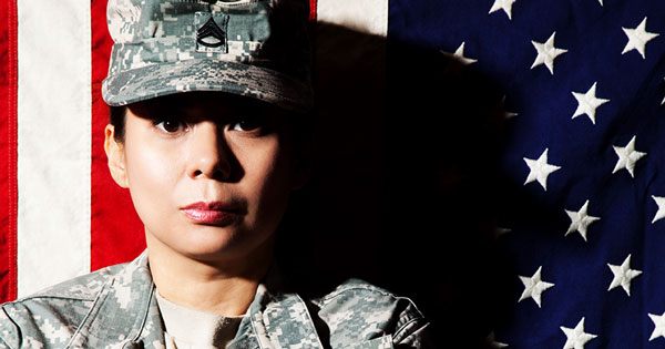 female veteran standing in front of the american flag