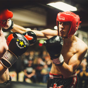 Two men wearing helmets boxing with one punching the other in a ring.