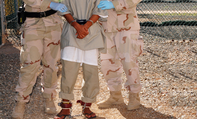 Guards from the Navy Expeditionary Guard Battalion escort a detainee into the medical facility in Guantanamo Bay Detainment Camp Four Nov. 23, 2007.