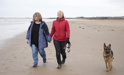 Mature female couple laughing and holding hands walking along the beach on a cold day