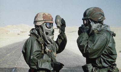 Two US soldiers wearing Nuclear Biological and Chemical protective outfits for a training exercise in Saudi Arabia before the start of operations in Kuwait.