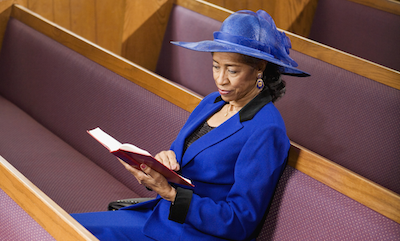 Senior African American woman sitting in pews reading Bible
