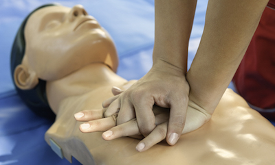 Hands performing chest compressions on CPR dummy