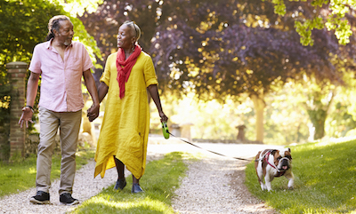 Senior African American couple down country road with their bulldog