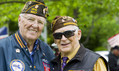 Two Massachusetts veterans of WWII and the Korean War pose together at an outdoors Memorial Day service