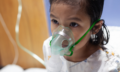 Young Thai child wearing inhaler mask