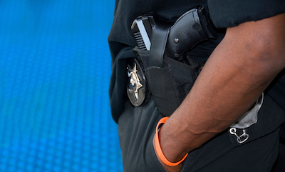 Close-up on an African American police officer's arm and belt, with his gun in the middle of the image