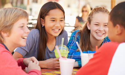 Diverse group of 10-12 year olds hanging out drinking sugary drinks