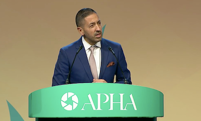 Dean Sandro Galea speaking at a podium that says APHA