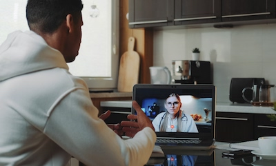 A young man on a video call with his doctor