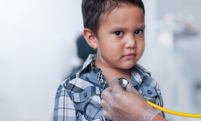 A young Hispanic boy having his heart listened to with a stethoscope