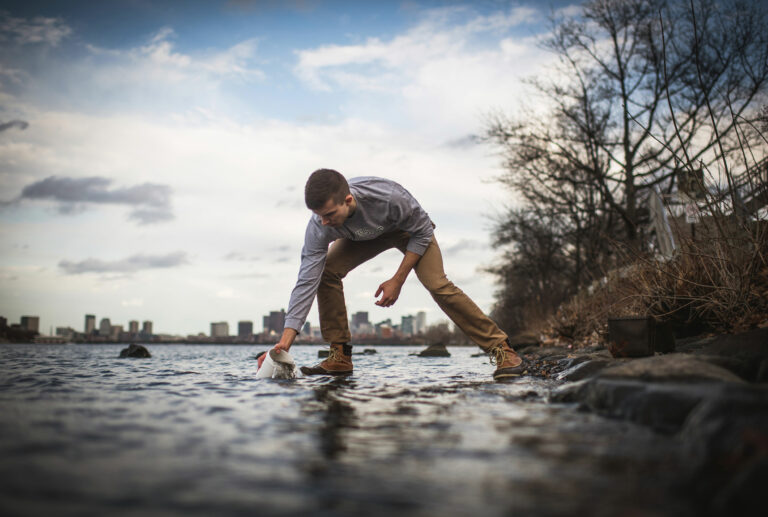 Photo of researcher collecting a sample out of a body of water.