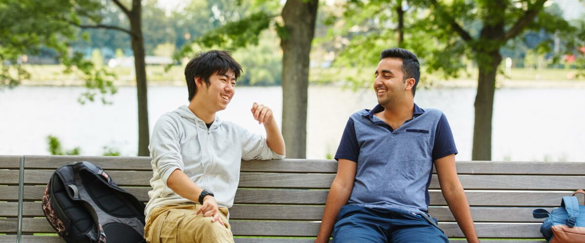 Two boys involved in the High School Honors program sitting on a bench along the Charles River.